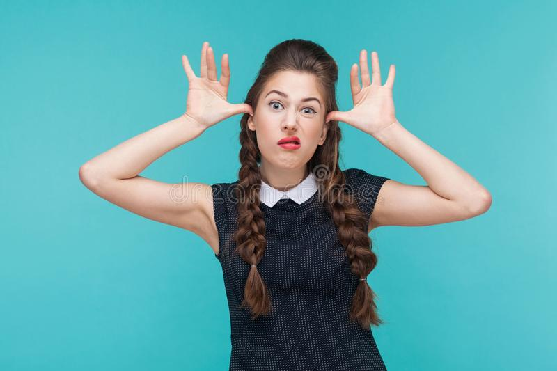Funny woman showing idiotic and comic face at camera. royalty free stock images