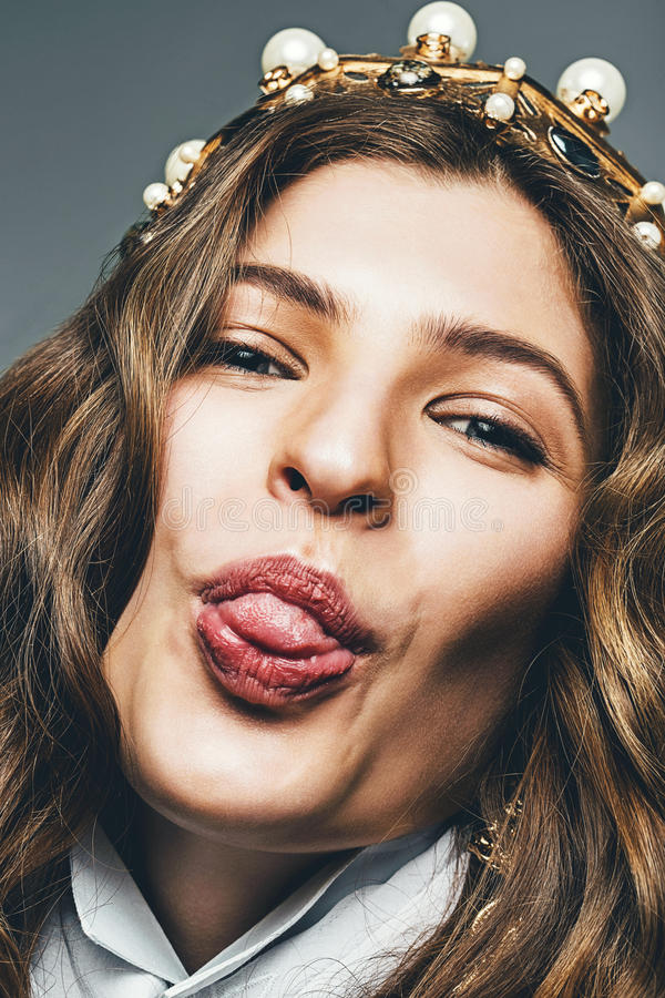 Funny woman shows tongue in crown royalty free stock image