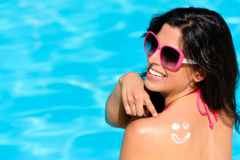 Funny woman on summer with sunscreen at swimming pool stock image