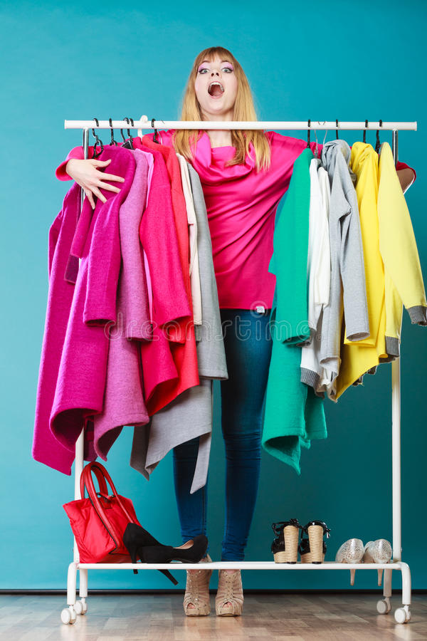 Funny woman taking all clothes in mall or wardrobe. Funny woman girl taking grabbing all clothes coats and shirts in wardrobe. Young girl shopping in mall stock photo