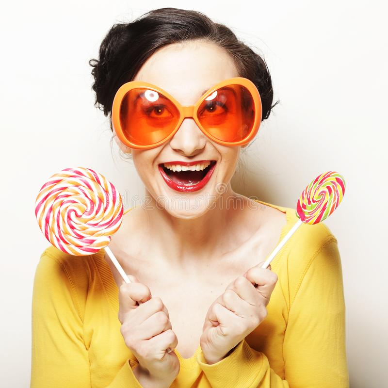 Woman wearing big sunglasses holding lollipop. Funny woman wearing big bright sunglasses holding lollipop royalty free stock photos