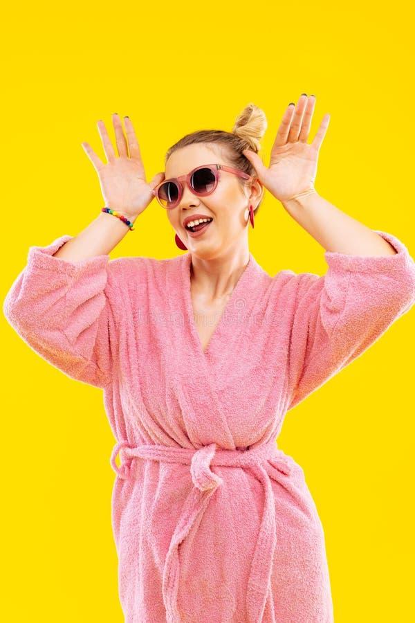 Funny woman wearing bright pink bathrobe making funny pose. Pink bathrobe. Funny blonde-haired young woman wearing bright pink bathrobe making funny pose stock photos