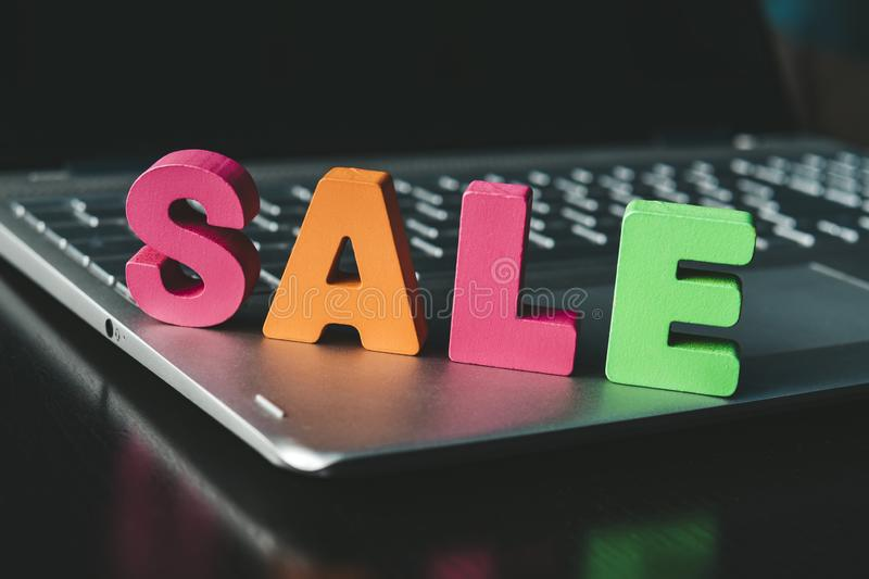 Funny word Sale set on notebook bottom. Colorful sign Sale on black surface at black screen background. Shopping online concept. Internet marketing. E-commerce royalty free stock images