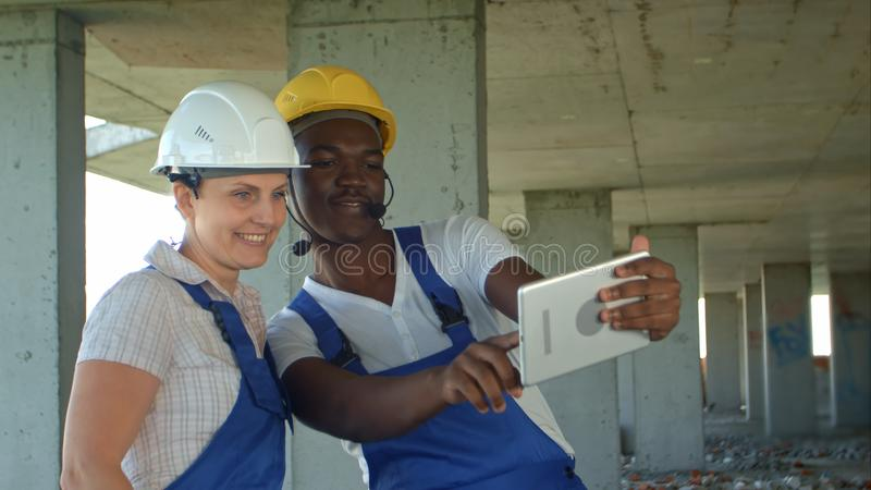 Funny workers taking selfie at contruction site. Close up. Professional shot in 4K resolution. 104. You can use it e.g. in your commercial video, business royalty free stock photography
