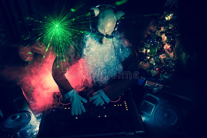 Dj Santa Claus at Christmas with glasses and snow mix on New Year's Eve event in the rays of light. Funny 2019 year of pig concept. Dj Santa with pig mask at stock image