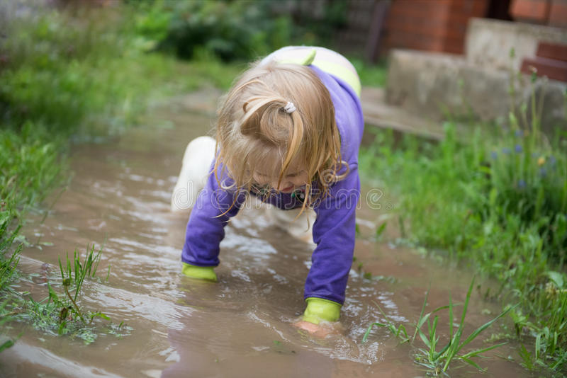Funny 2 years old baby girl playing in puddle. royalty free stock images