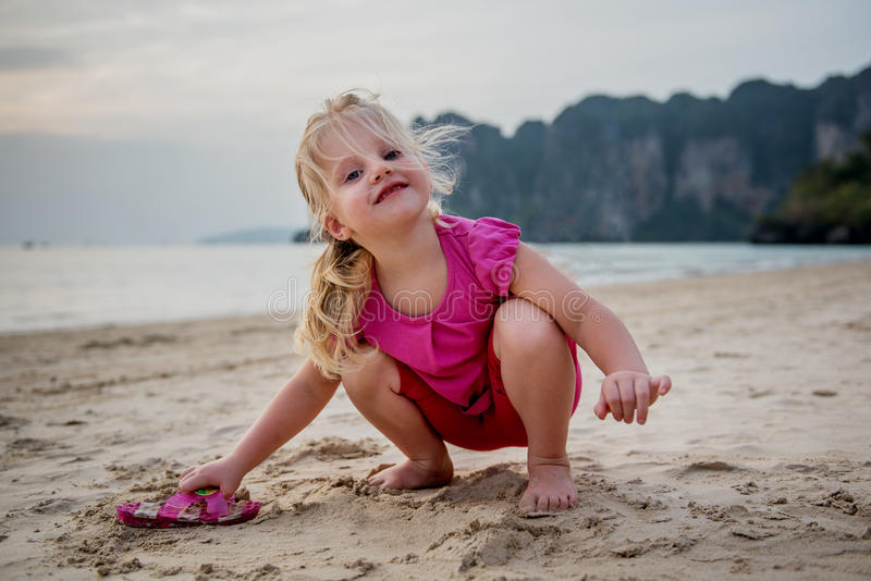 Funny 3 years old girl playing at the bech stock photos