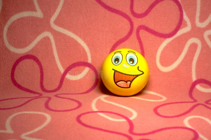 Funny yellow emoticon smiley rubber children ball on pink felt background. Happiness concept stock photo