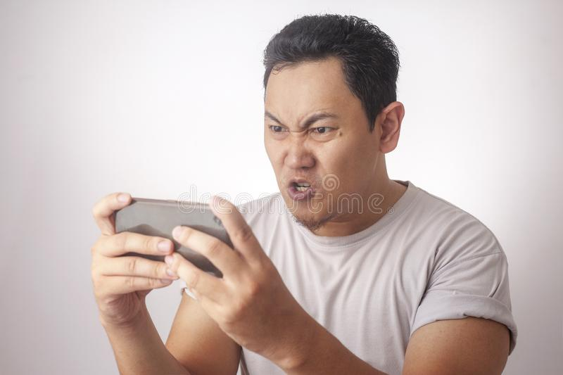 Funny Young Asian Guy Playing Games on Tablet stock images