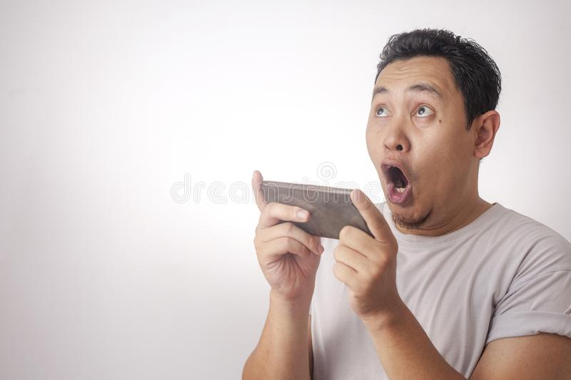 Funny Young Asian Guy Playing Games on Tablet Smart Phone. Photo image portrait of a cute handsome young Asian man with funny face playing games on tablet smart royalty free stock images