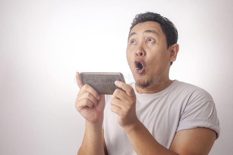 Funny Young Asian Guy Playing Games on Tablet Smart Phone. Photo image portrait of a cute handsome young Asian man with funny face playing games on tablet smart royalty free stock photo