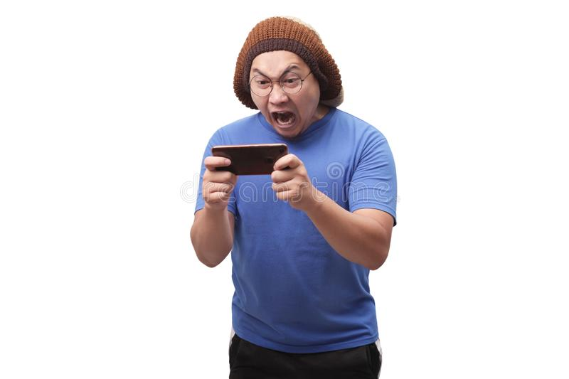Funny Young Asian Guy Playing Games on Tablet Smart Phone stock image