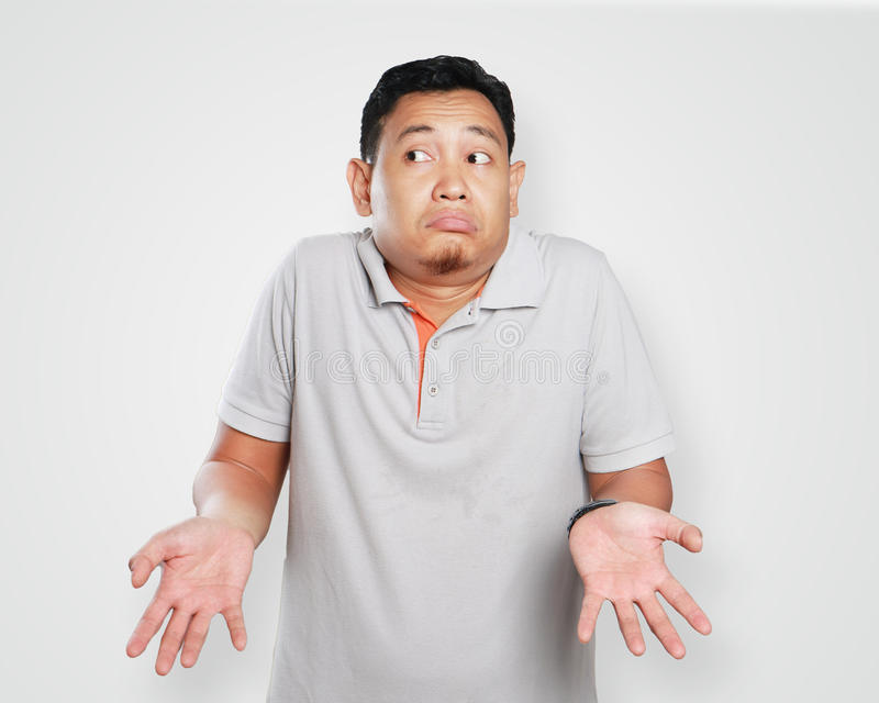 Funny Young Asian Guy Shrug Gesture. Photo image portrait of a cute young Asian man showing I don`t know gesture, shoulder shrug and looking to the side stock image