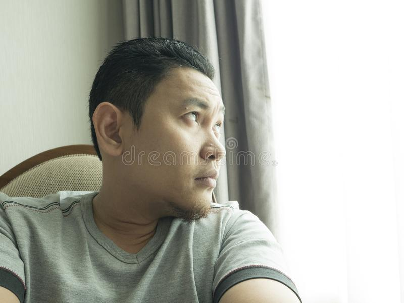Funny Young Man Thinking Expression, Looking to The Side. Funny young Asian man wearing casual grey shirt thinking, looking to the side. Close up body portrait royalty free stock photography