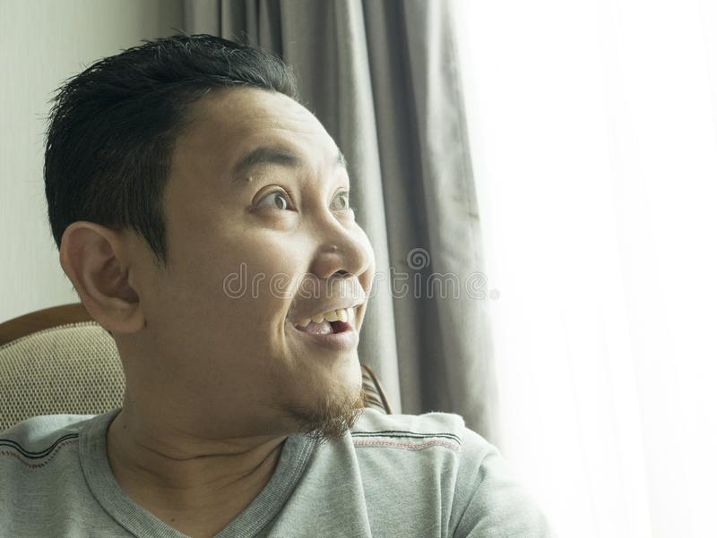 Funny Young Man Thinking Expression, Looking to The Side. Funny young Asian man wearing casual grey shirt thinking, looking to the side. Close up body portrait stock photo