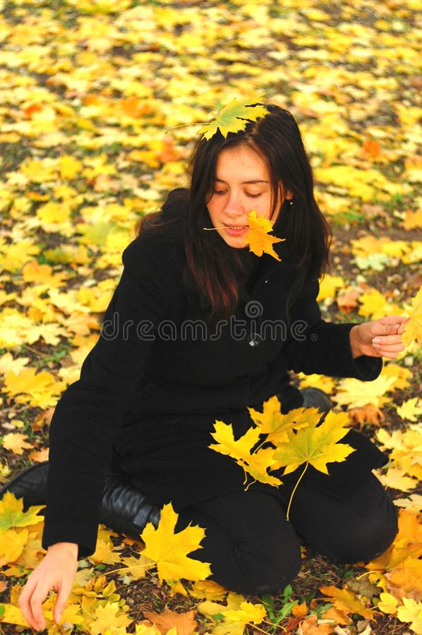 A funny young attractive girl has fun and fooling around in an autumn park. Cheerful emotions, autumn mood.  stock photography