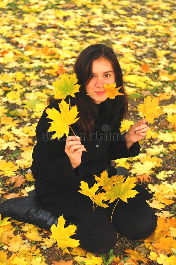 A funny young attractive girl has fun and fooling around in an autumn park. Cheerful emotions, autumn mood.  royalty free stock photo