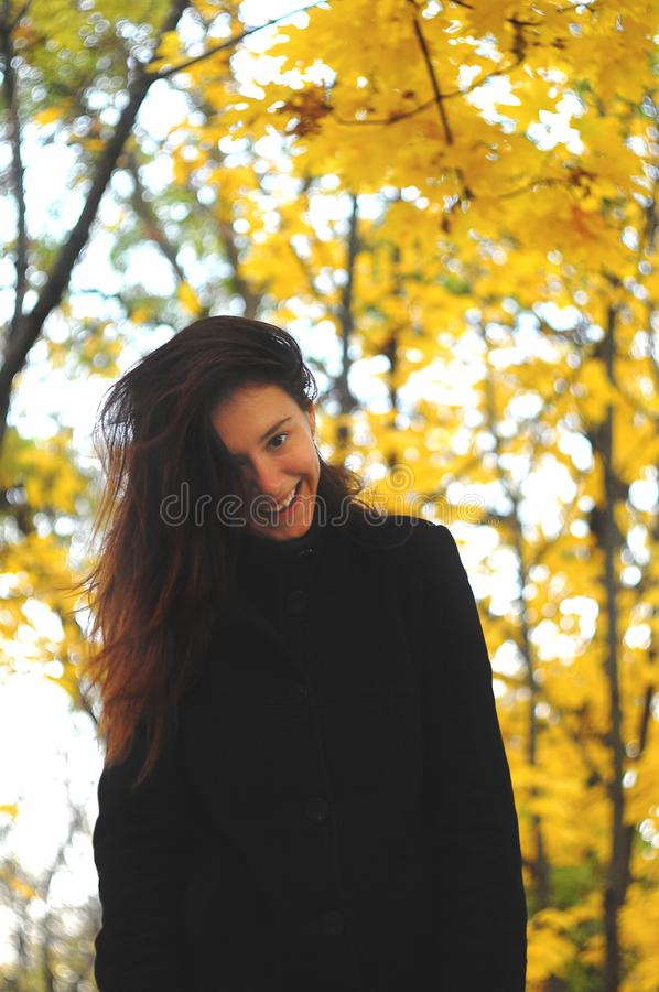 A funny young attractive girl has fun and fooling around in an autumn park. Cheerful emotions, autumn mood.  stock photo