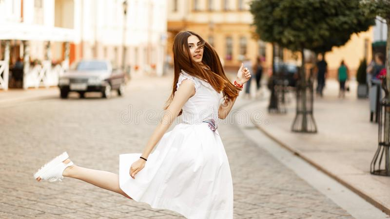 Funny young beautiful woman in white dress walking in the city. royalty free stock images
