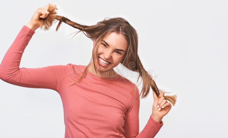 Funny young blonde woman with playing with her hair, dressed casual pink long sleeve blouse, making funny faces at camera, smiling stock images