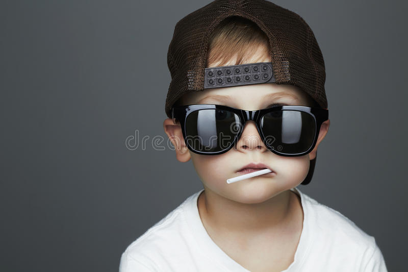 Funny Young Boy Eating A Lollipop.child in sunglasses. Funny Young Boy Eating A Lollipop.Fashionable child in sunglasses royalty free stock images