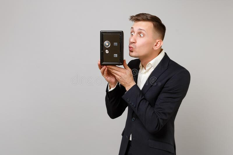 Funny young business man in suit blowing sending air kiss to metal bank safe for money accumulation in hand isolated on. Grey background. Achievement career stock images