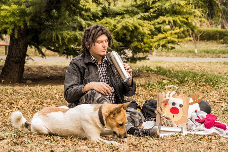 Funny young caucasian man with afro hairstyle on the picnic with his dog stock photo
