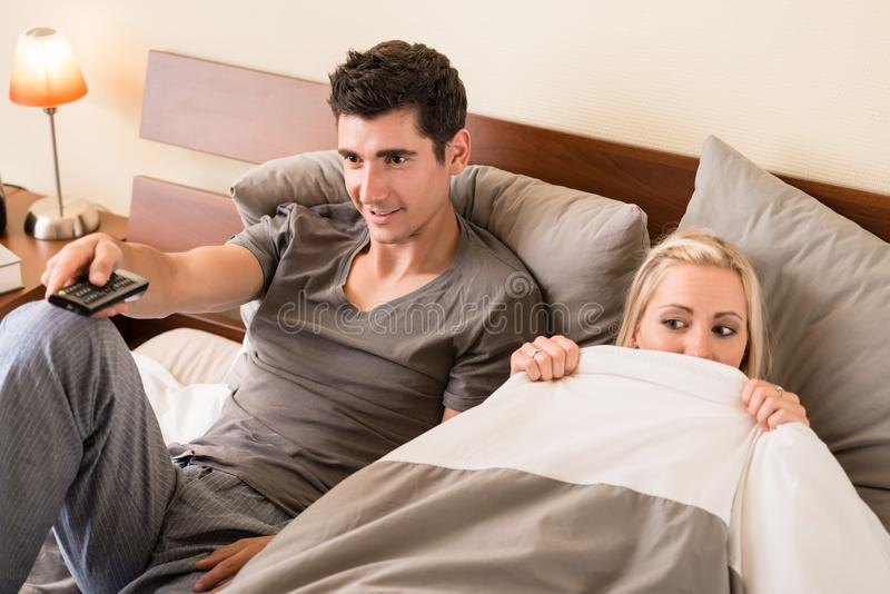Couple sitting in bed while watching TV. Funny young couple sitting in bed while watching TV together at night royalty free stock photo