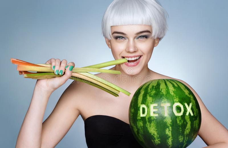 Funny young girl bites celery stock photo