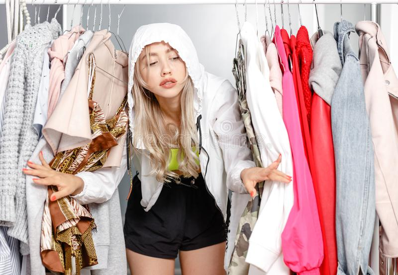 Funny young girl blogger dressed in fashionable clothes standing between clothes hanging on a hanger in the wardrobe stock image