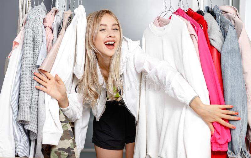 Funny young girl blogger dressed in fashionable clothes standing between clothes hanging on a hanger in the wardrobe stock photography