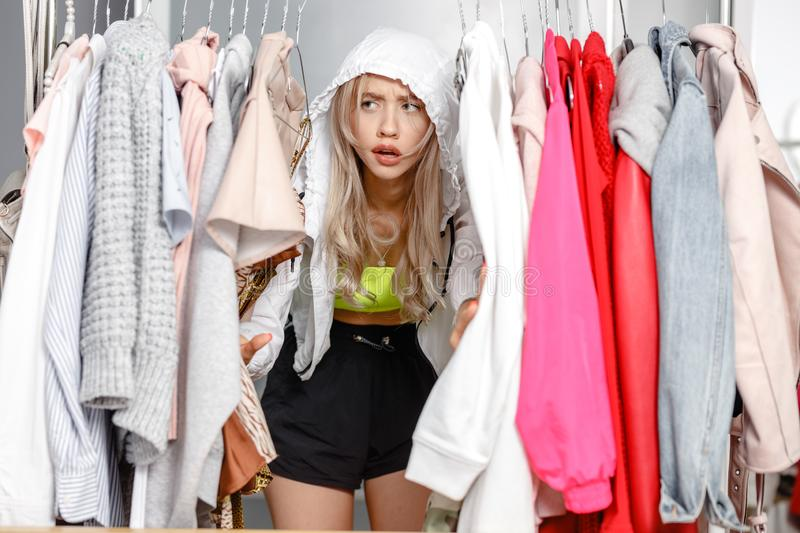 Funny young girl blogger dressed in fashionable clothes standing between clothes hanging on a hanger in the wardrobe royalty free stock image