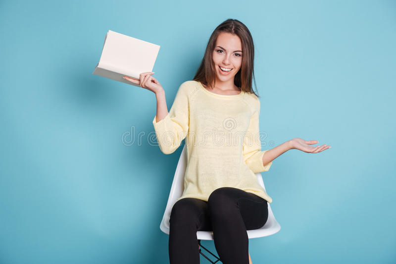 Funny young girl with a book over blue background royalty free stock photography