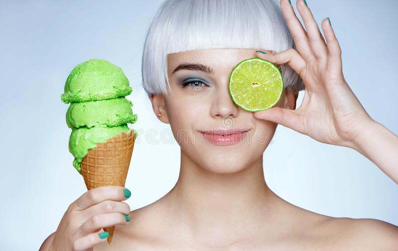 Funny young girl holding waffle cone with ice cream and green lime stock image