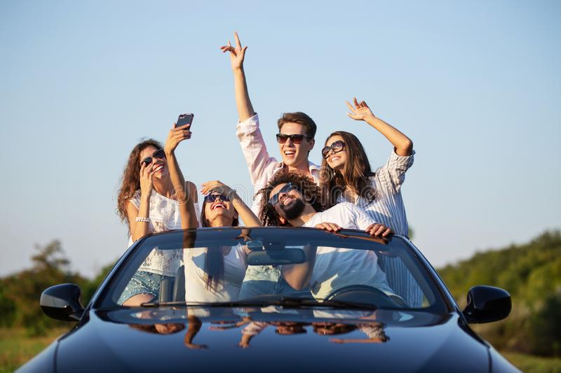 Funny young girls and guys in sunglasses are sitting in a black cabriolet on the road holding their hands up and making stock images