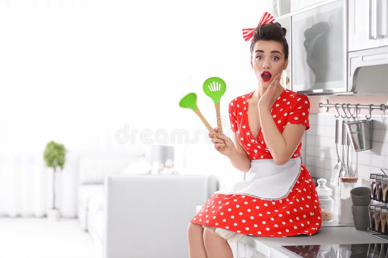 Funny young housewife with cooking utensils royalty free stock photo