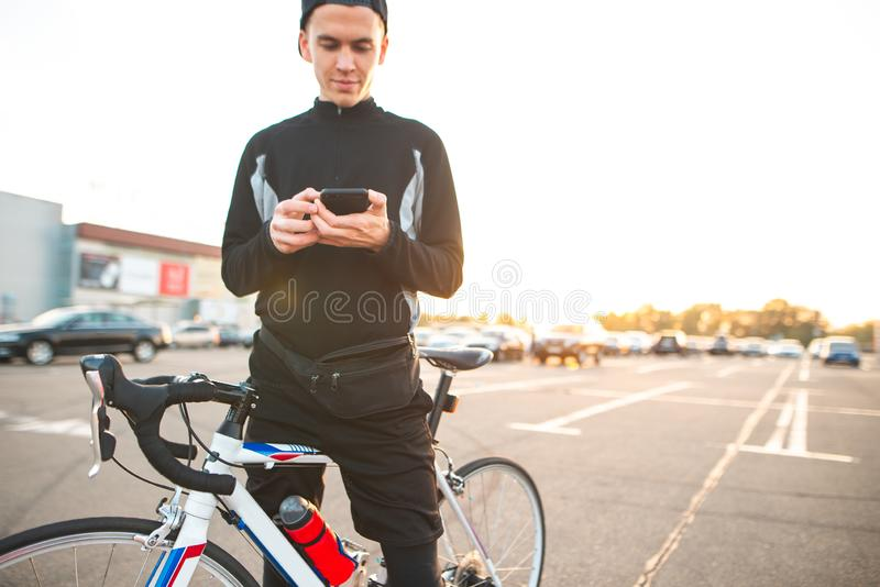Funny young man with a bicycle is standing against the background of the sunset stock photos