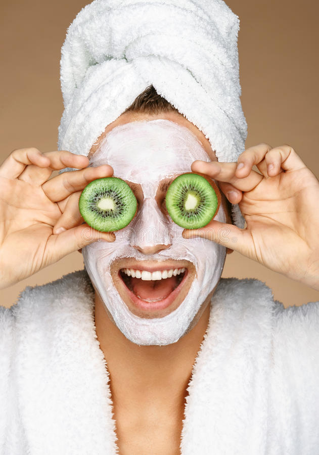 Funny young man with facial mask and pieces of kiwis on eyes. stock image
