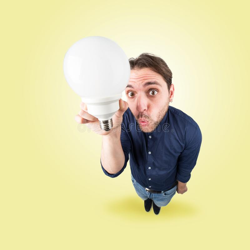 Funny young man with light bulb in his hand. From above stock photos