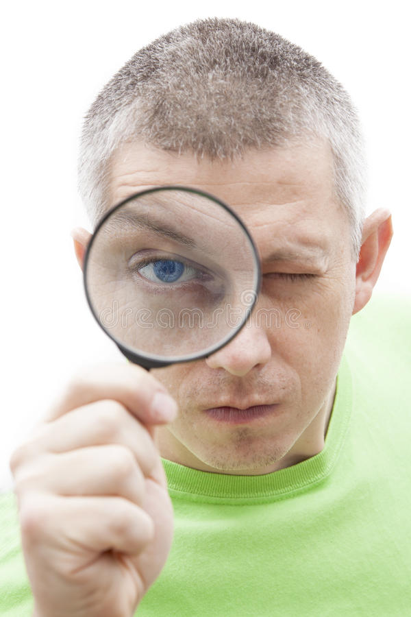 Funny young man looking through magnifying glass royalty free stock photo
