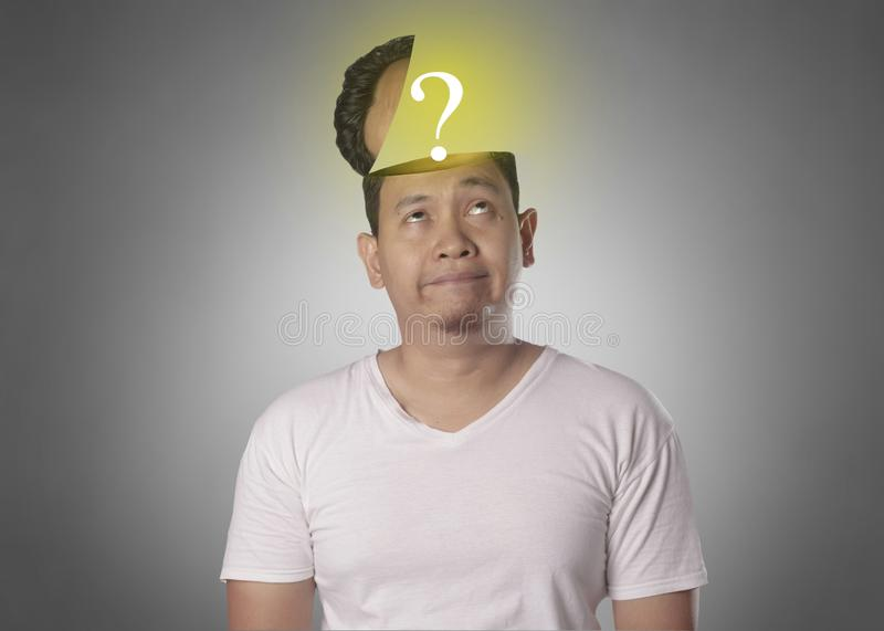 Funny Young Man Thinking Expression With Question Mark in His Open Head royalty free stock image
