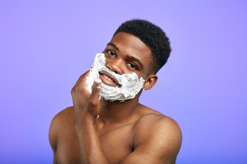 Funny young man touching his chin with foam royalty free stock images