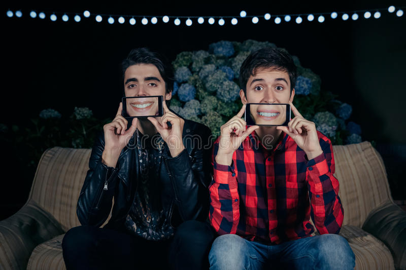 Funny young men holding smartphones showing female. Closeup of two funny young men holding smartphones over their faces showing female mouths smiling in the stock photography