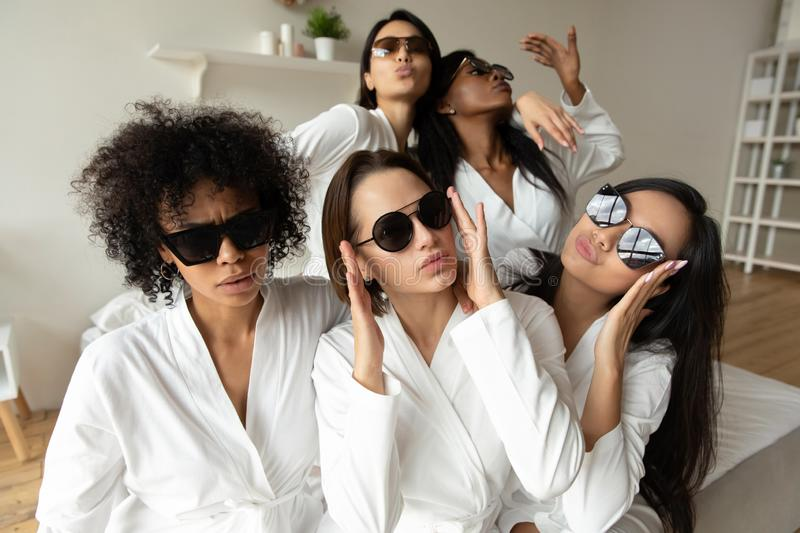 Funny young multiracial girls wear sunglasses bathrobes looking at camera royalty free stock photo