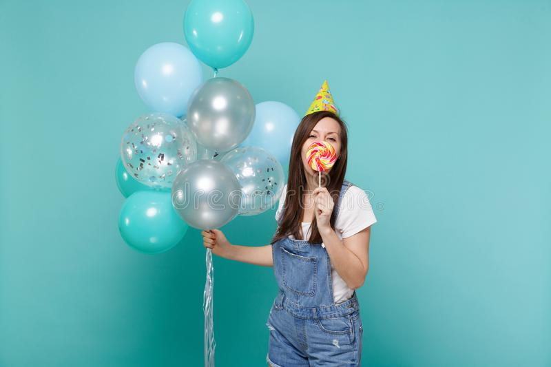 Funny young woman in birthday hat covering mouth with round lollipop celebrating hold colorful air balloons isolated on. Blue turquoise wall background stock images