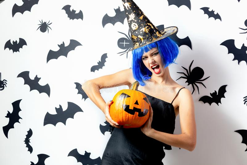 Funny young woman in a blue wig and witch`s hat holds Halloween pumpkin on a white background with black bats and stock photography