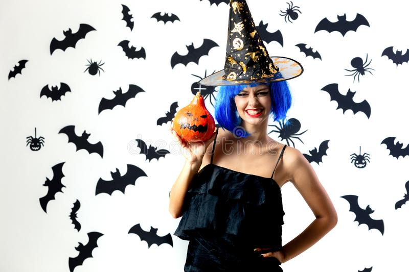 Funny young woman in a blue wig and witch`s hat holds Halloween pumpkin on a white background with black bats and stock images