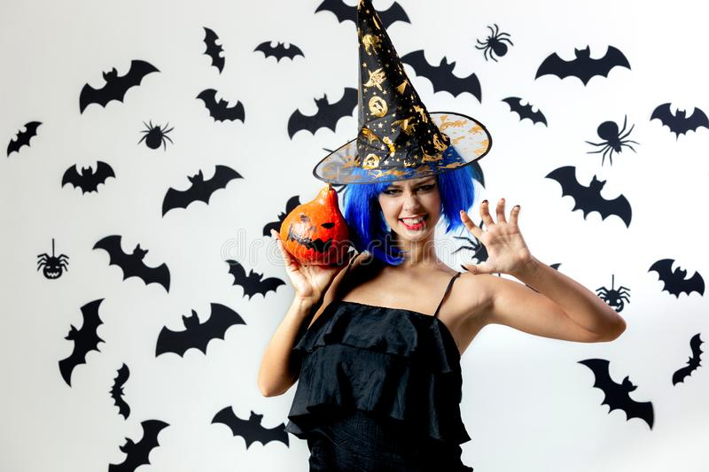 Funny young woman in a blue wig and witch`s hat holds Halloween pumpkin on a white background with black bats and royalty free stock photos