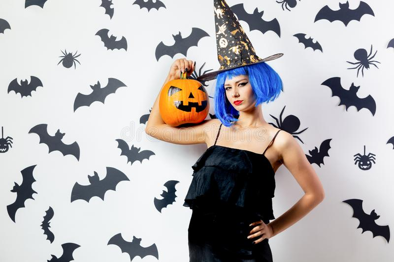Funny young woman in a blue wig and witch`s hat holds Halloween pumpkin on a white background with black bats and royalty free stock images