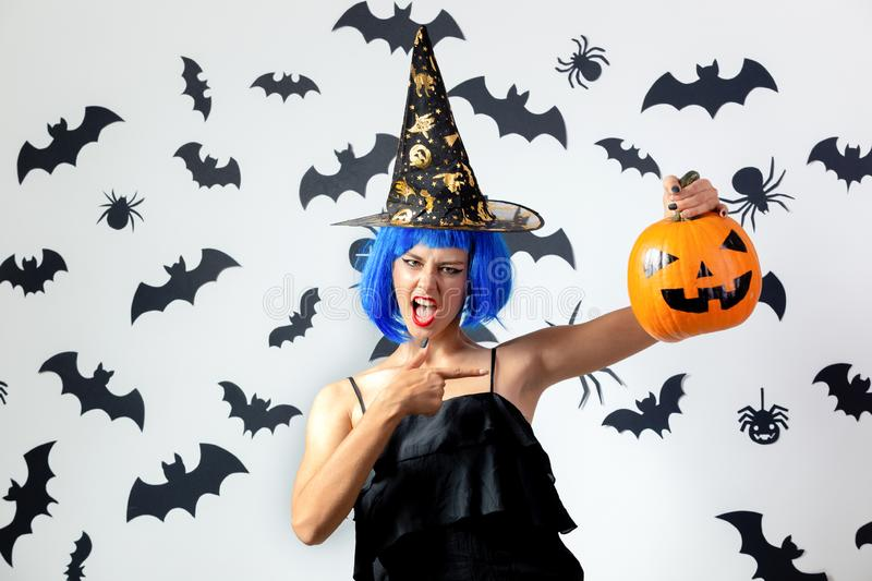 Funny young woman in a blue wig and witch`s hat holds Halloween pumpkin on a white background with black bats and royalty free stock image